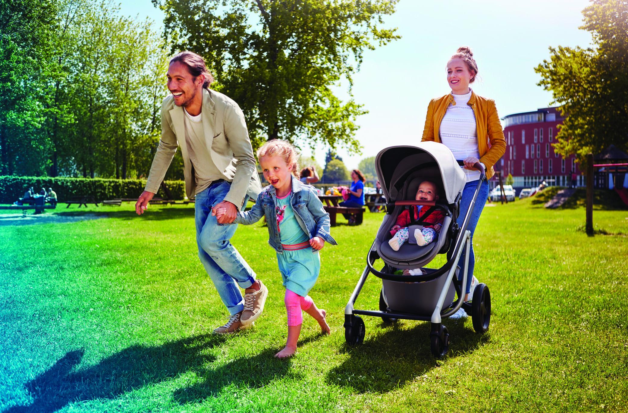 BBC1311_2018_bebeconfort_stroller_Lila_Lifestyle_Spring-Playground_dadandgirlrunningupfrontmumstrolling_Landscape