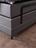 Boxspringbett mit grauem Stoff, schwarzen Metallfüßen und motorisierter Kopf-und Fußverstellung