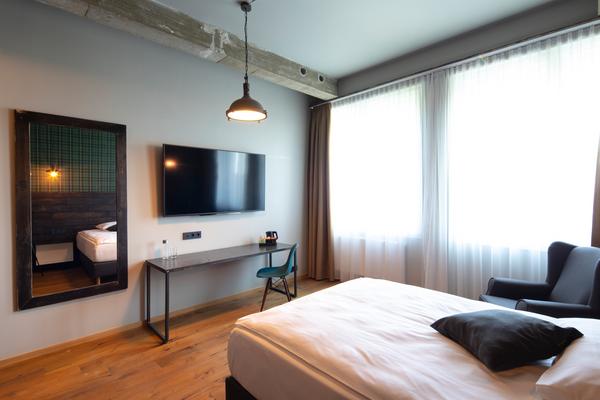 Ohrensessel Witold in blau | Hotelzimmer mit Fernseher und Spiegel im Loftstyle Hotel