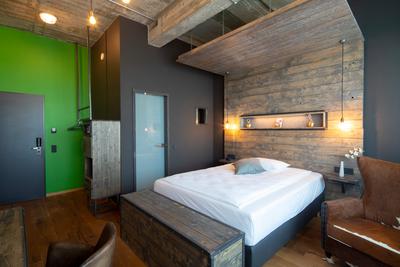 Clubsofa Witold im Kuhflecken-Look | Hotelbett Silent in grau gepolstert | Hotelzimmer mit Holzvertäfelung im Loftstyle Hotel