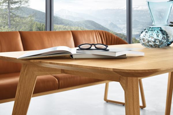 Holztisch der Essgruppe Cliff mit offenem Buch und Brille.