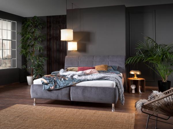 Bett in grauem Stoff, mit geteiltem Bettkasten und Quadratheftung im Kopfhaupt