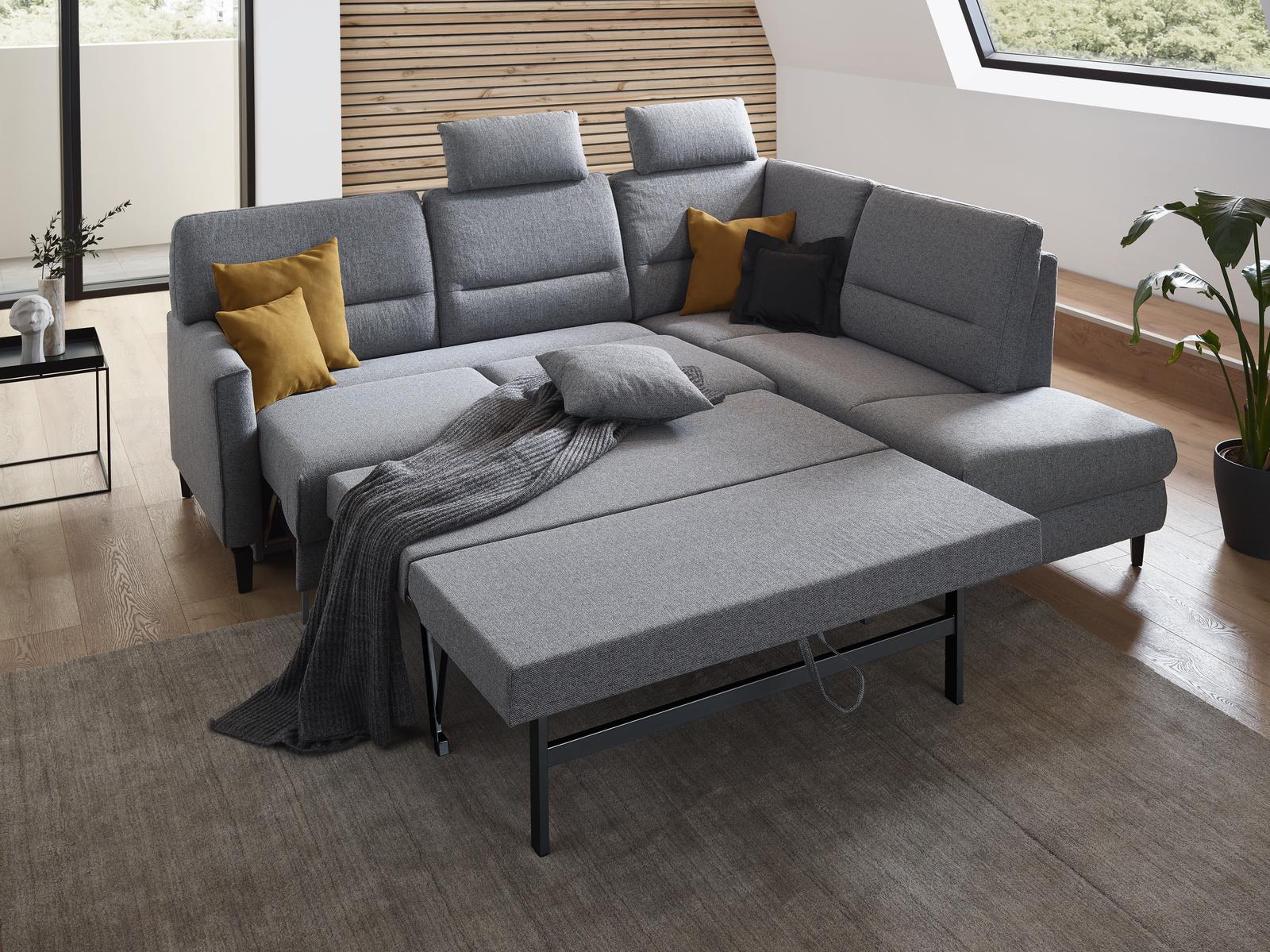 Ecksofa Messina in grauem Stoff mit Schlaffunktion und schwarzen Möbelfüßen.