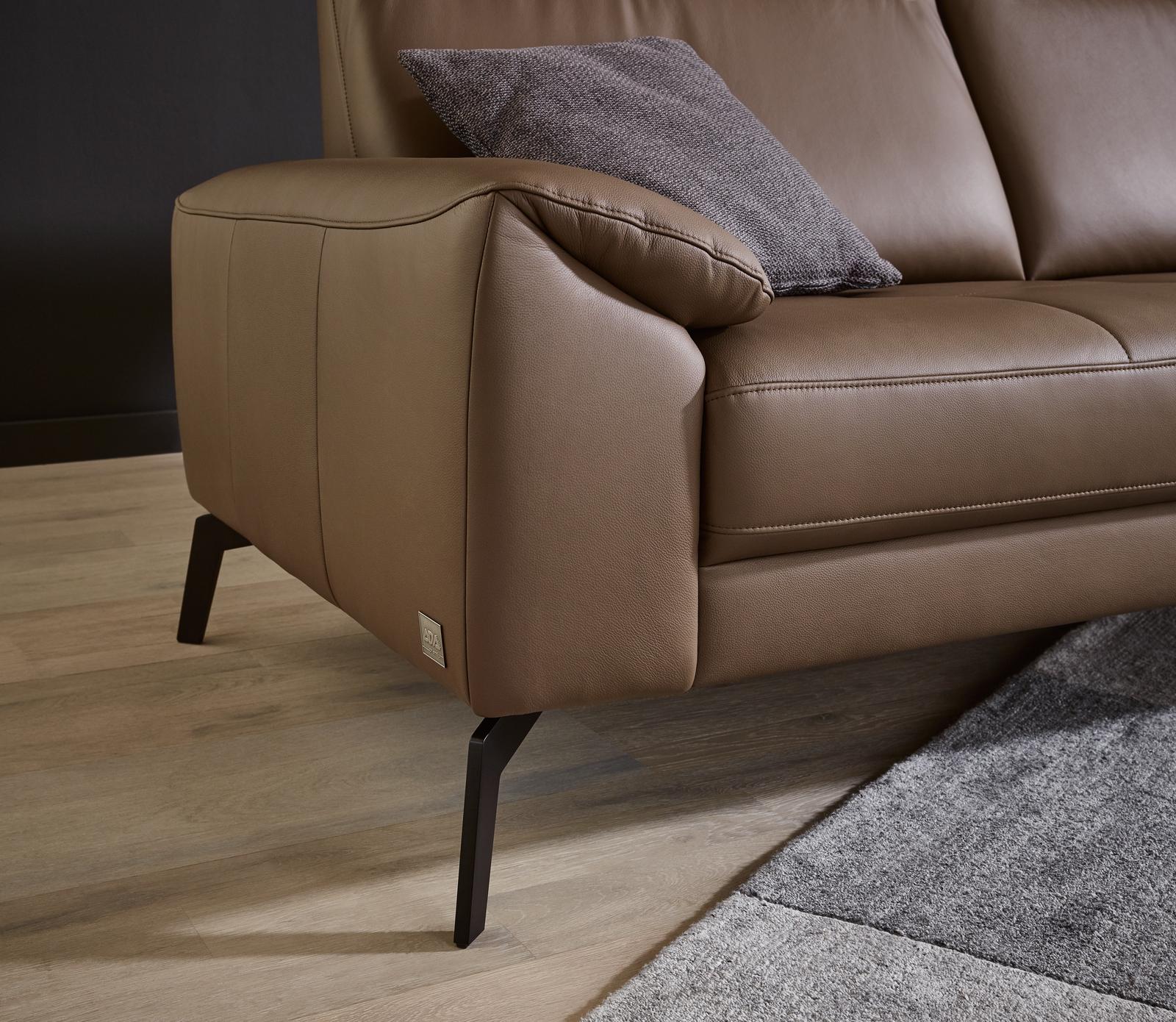 Armteil des Sofas Wales in braunem Leder mit schwarzen Metallfüßen.
