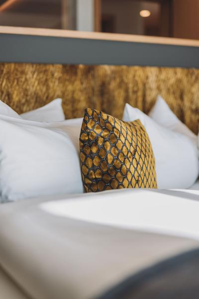 Kissen Sonderanfertigung mit kundenspezifischem Stoff in gelb und schwarz   Detailaufnahme vom Hotelbett im Hotel Rosenalp