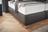 Boxspringbett in dunkelbraunem Leder, Holzfüßen und Knopfheftung im Kopfhaupt
