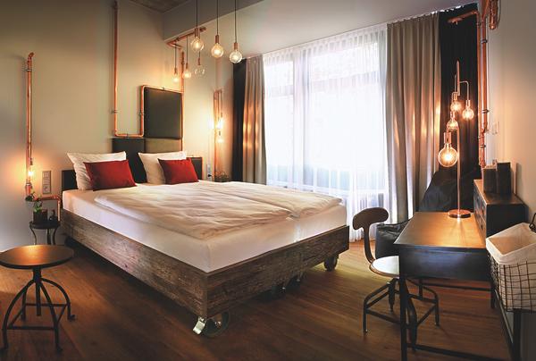 Mobiles Holzbett mit Rollen und gepolstertem Sonder-Kopfteil in Schachbrettmuster in braun und grün | Hotelzimmer mit Schreibtisch im Loftstyle Hotel