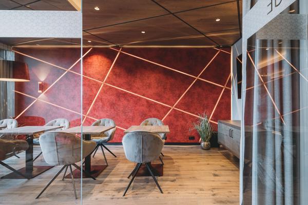 Clubsessel Sonderanfertigung mit grauem Samtbezug | Hotellobby mit roter Wand und Beleuchtung im Hotel Rosenalp