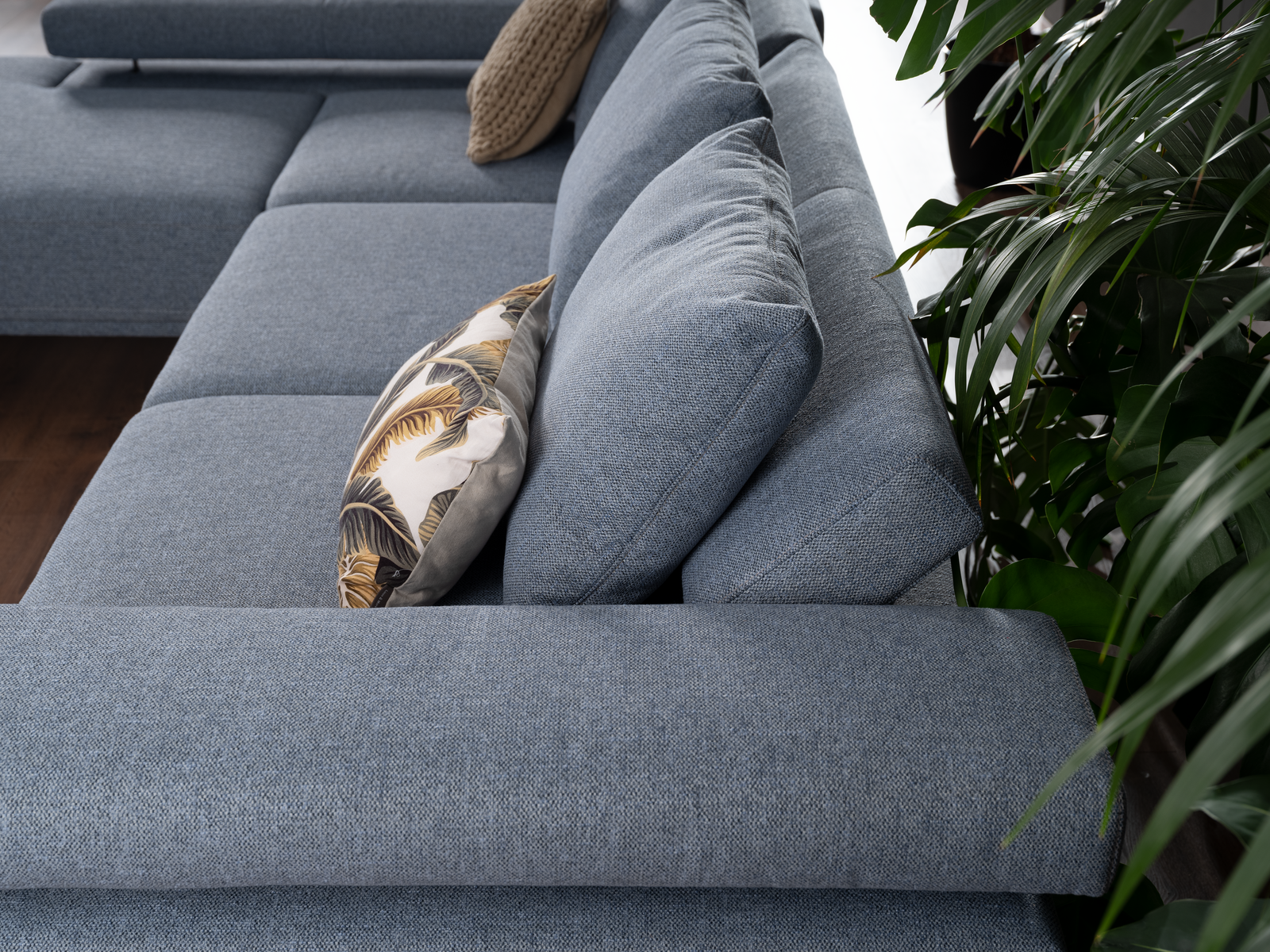 Detailbild von Sofa Roger in hellblauem Stoff, losem Rückenkissen und verstellbarer Armlehne.
