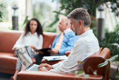 Mann mit Notebook auf einem braunen Sofa | Newsbeitrag wir erweitern unser Sortiment