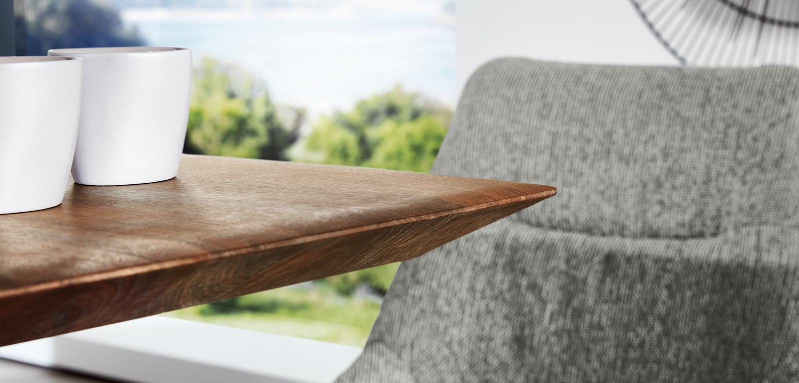 Lehnensteppung des Sessel Preston in grauem Stoff mit Ecke des Holztisches.