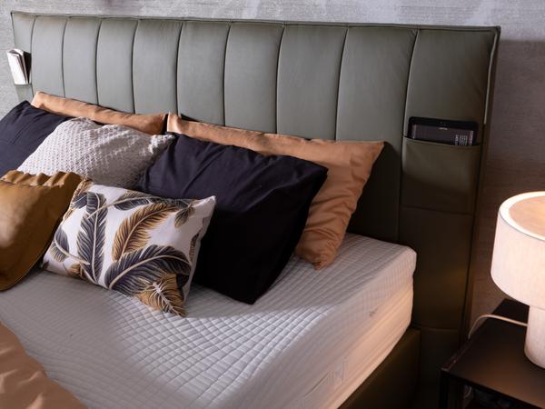 Bett in grünem Lederstoff, schwebender Optik und Einstecktaschen am Kopfhaupt