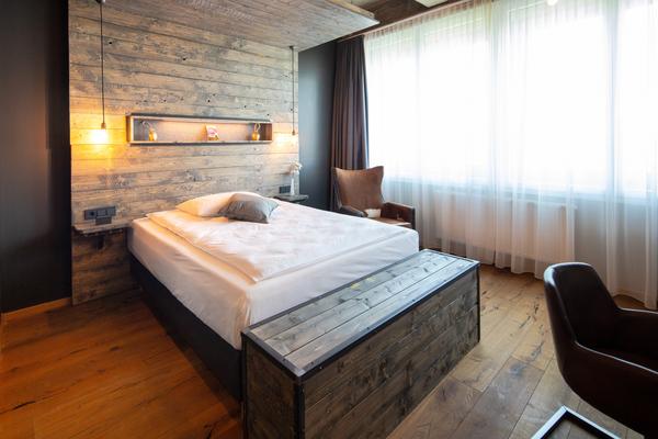 Ohrensessel Witold in braun | Hotelbett Silent in grau | Hotelzimmer mit Holzvertäfelung im Loftstyle Hotel
