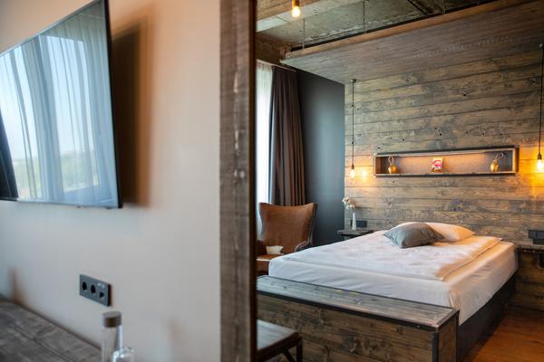 Polstersessel Witold in braun | Bettkasten Silent in blau gepolstert | Hotelzimmer mit Holzvertäfelung im Loftstyle Hotel