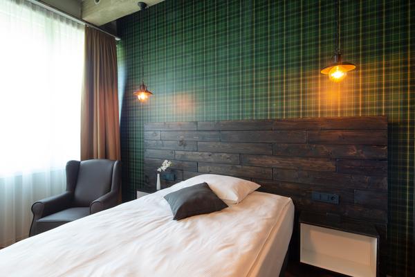 Armchair Witold in braunem Kunstleder | Hotelbett Kopfteil Sonderanfertigung in Holzlatten-Optik mit Aussparungen für Nachtkästchen | Hotelzimmer im Loftstyle Hotel