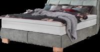 Bett mit grünem Stoff, breiten Holzfüßen und Naht im Kopfhaupt
