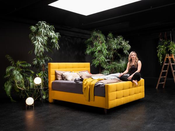 Bett in gelbem Stoff, schwarzen Holzfüßen und Quadratheftung im Kopfhaupt