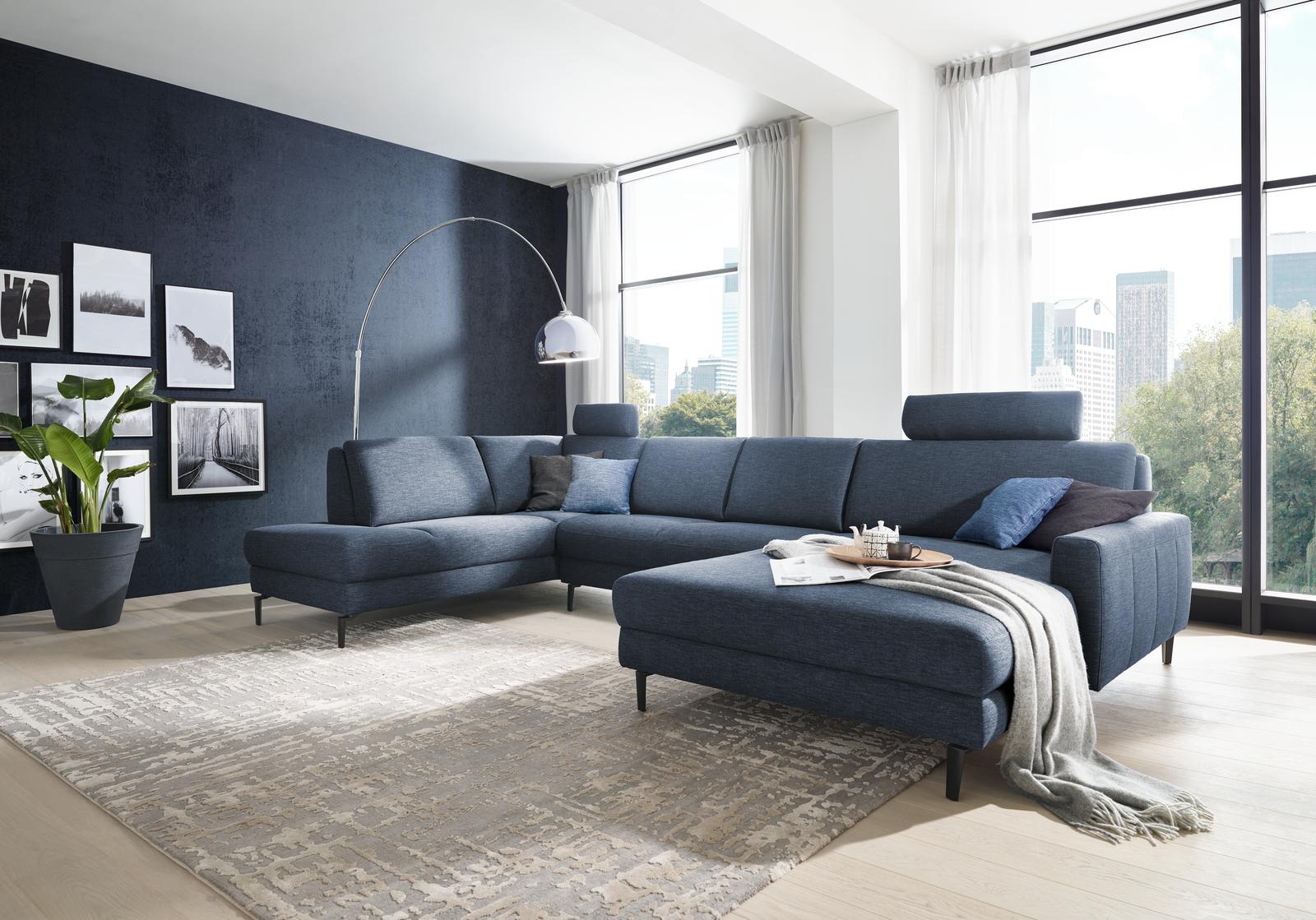 Wohnlandschaft Sandy in blauem Stoff und U-Form mit schwarzen Möbelfüßen.