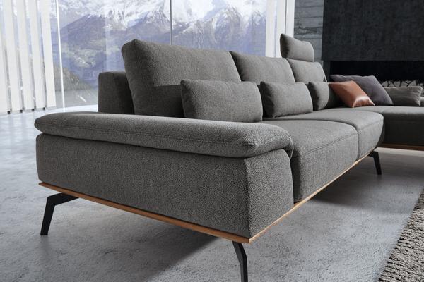 Armteil und Sitzfläche der Wohnlandschaft Santiago in grauem Stoff mit Holzsockel und schwarzen Möbelfüßen.