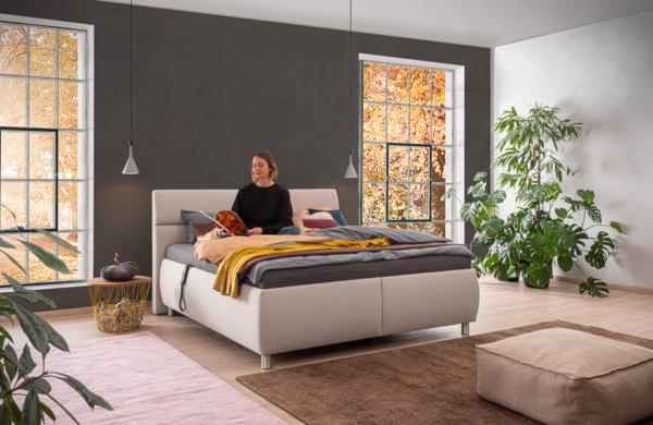 Bett in hellbeigem Stoff und motorisierter Kopf-und Fußverstellung