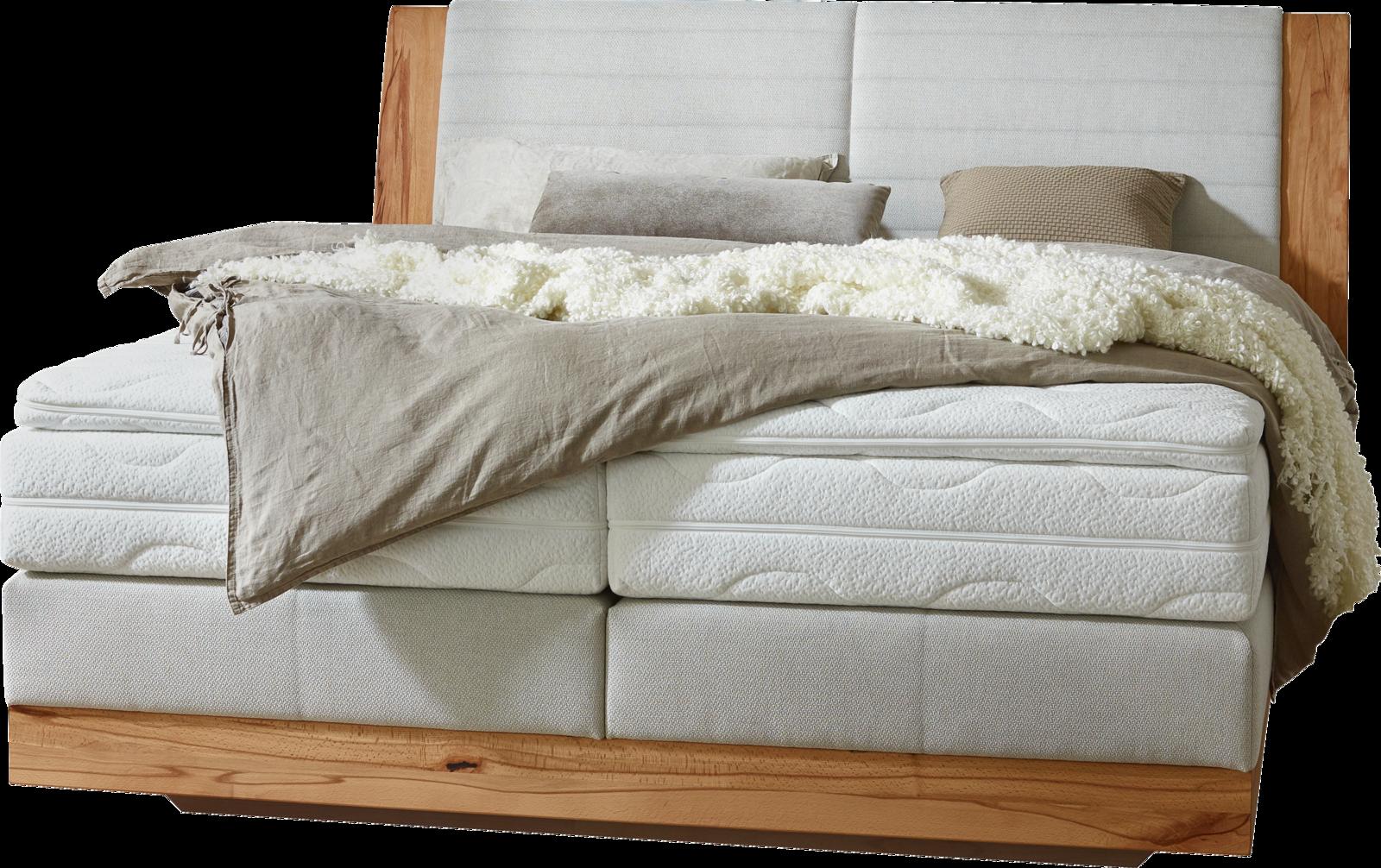 Boxspringbett in hellgrauem Stoff und geschichtetem Matratzenaufbau, Massivholzumrandung am Kopfhaupt und Holzsockel