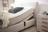 Boxspringbett in hellbeigem Stoff, Holzfüßen und motorisierter Kopf-und Fußverstellung