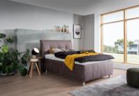 Bett in braunem Stoff, Chromfüßen und großen Bettzeugraum