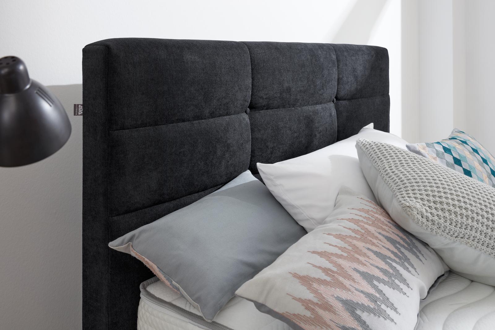 Bett in schwarzen Stoff, Quadratheftung im Kopfhaupt und Chromfüßen