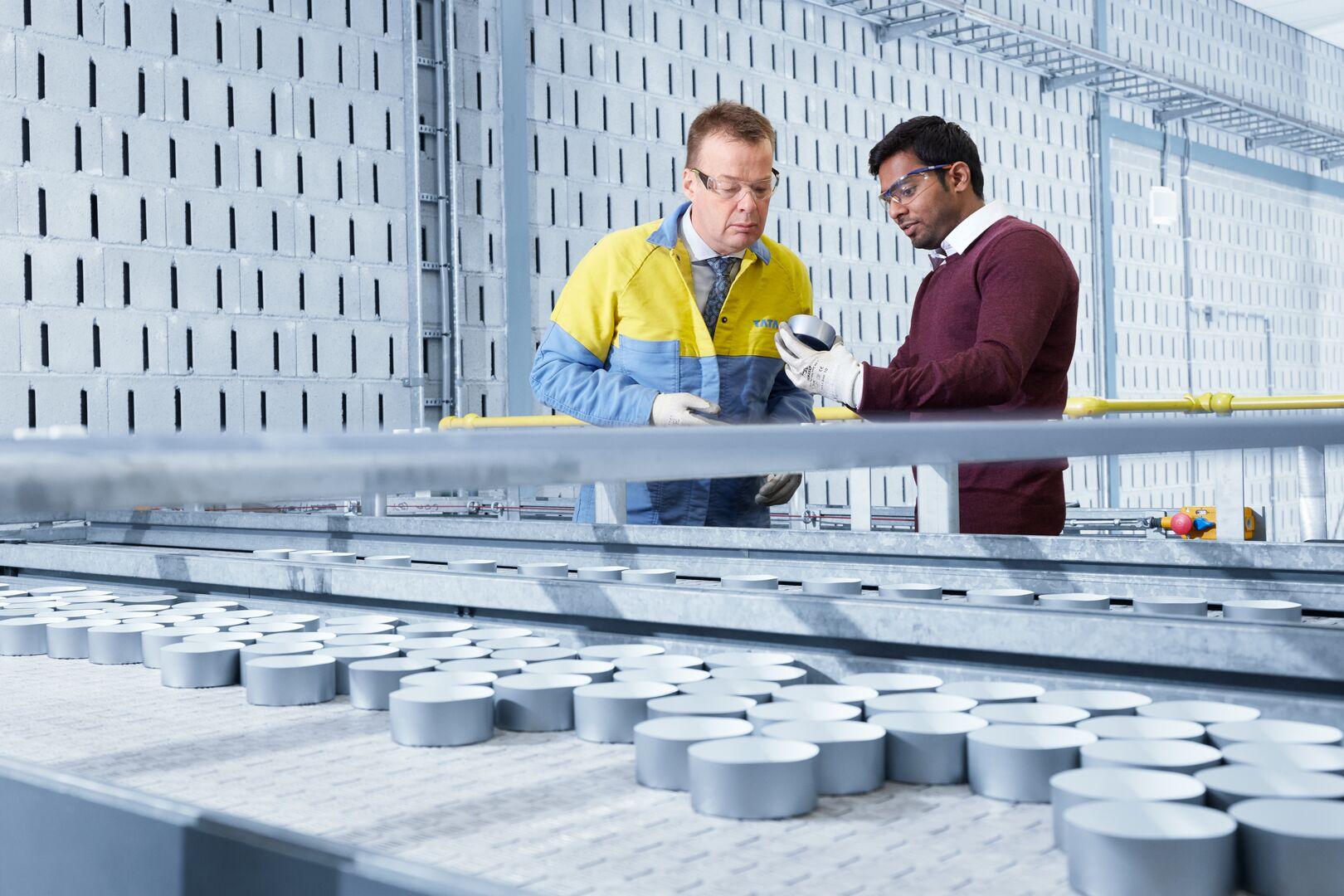 Tata Steel employees examining packaging can products at a testing facility