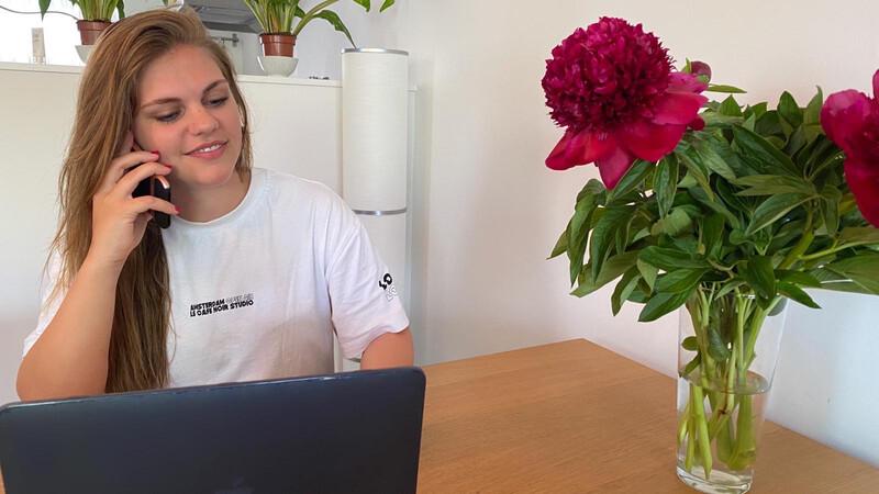 Vrijwilliger Nikki Vierboom, een jongedame met lang bruin haar in wit t-shirt zit achter een tafel met laptop en heeft mobiele telefoon aan haar oor