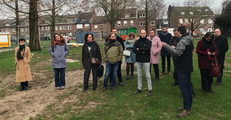 Een aantal mensen staat met winterjassen aan op een grasveld: een Europese delegatie bezoekt Superlocal een project van circulair bouwen in Kerkrade