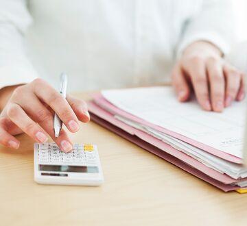 En person som skriver og regner på en kalkulator samtidig