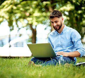 Mann sitter på gresset med en laptop