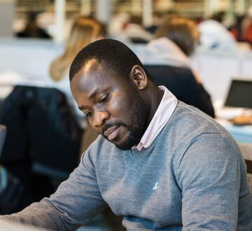 Male PhD candidate in the library at campus Oslo