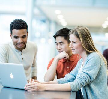 En gruppe med studenter ser på en PC-skjerm