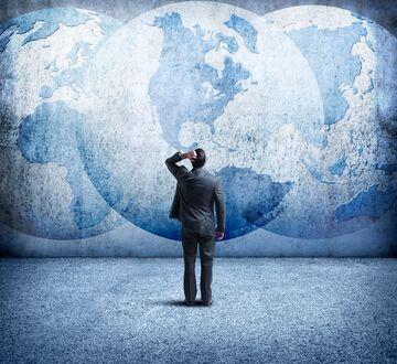 Mann i derss som ser opp på en vegg med et maleri av en jordklode