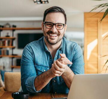 Mann bak PC smiler til kamera