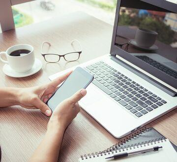 En pc, mobiltelefon og et par briller ligger på et bord