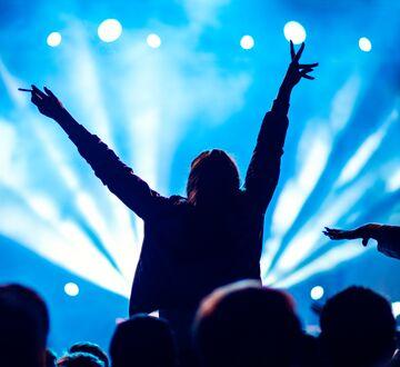 Person på konsert med armene over hodet