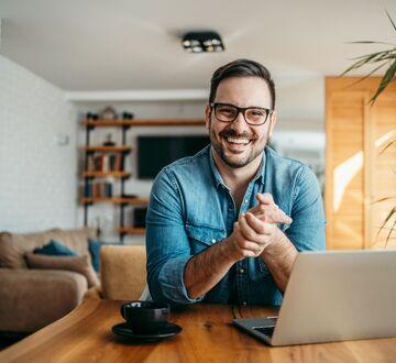 En mann som jobber smilende på sin datamaskin