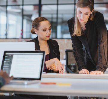 To kvinner som prater sammen i et kontorlandskap