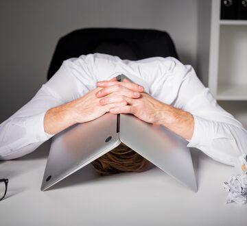 Frustrert mann gjemmer seg under en laptop