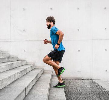 Mann løper opp en trapp