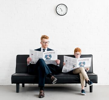 """Father and son in suits reading newspaper with the headline """"Business"""""""