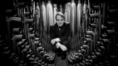 A man in front of an organ pipe