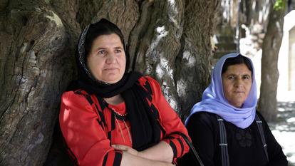 FKE3TY Two yazidi women resting beside a old tree in Lalish, Yazidis Holy temples in Kurdistan Iraq.