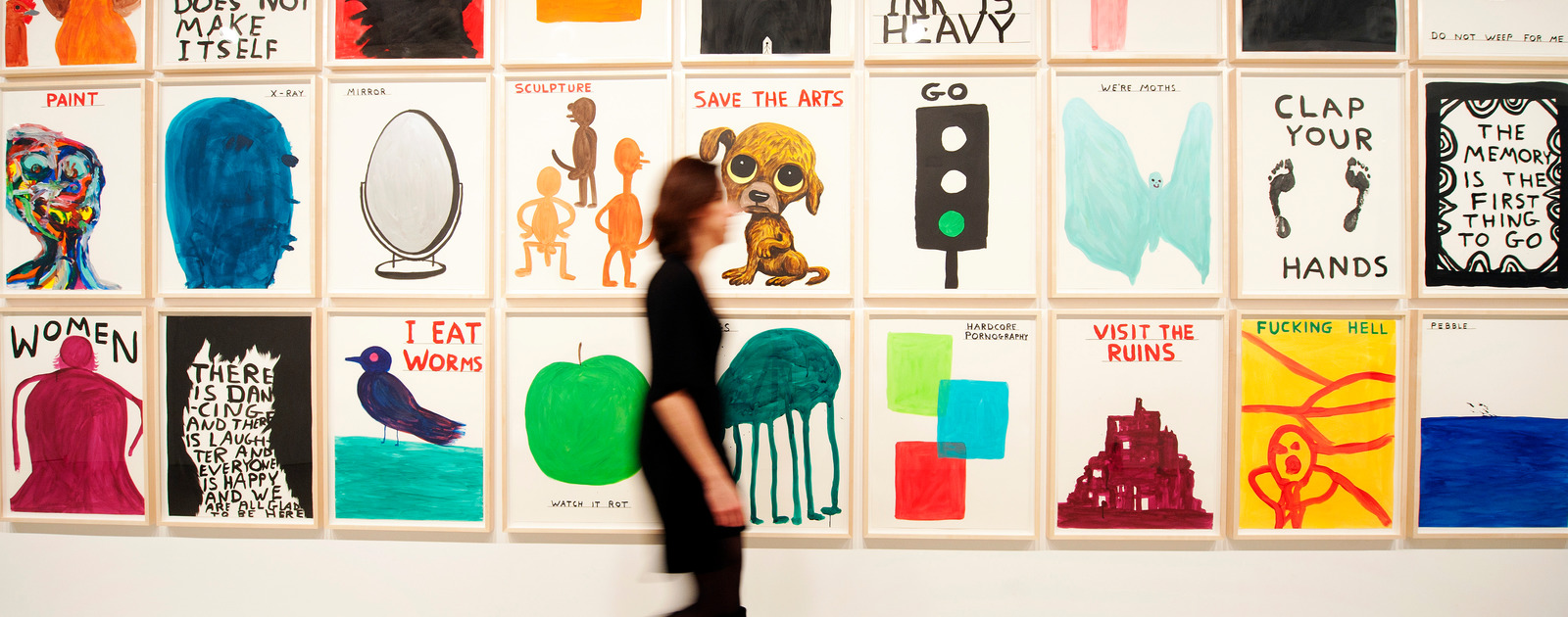 Visitor walking past illustrations by David Shrigley at Hayward Gallery