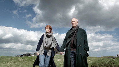 A woman and a man holding hand in a field