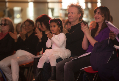 Couple with child clapping in audience