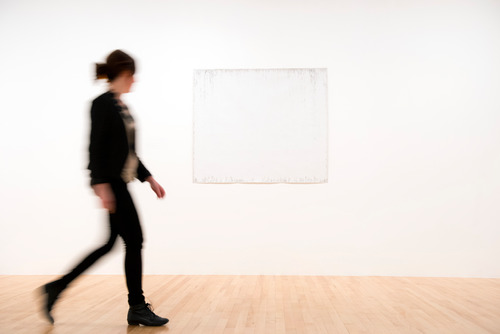 Visito Walking Past White Painting by artist,  Bruno Jakob at Hayward Gallery